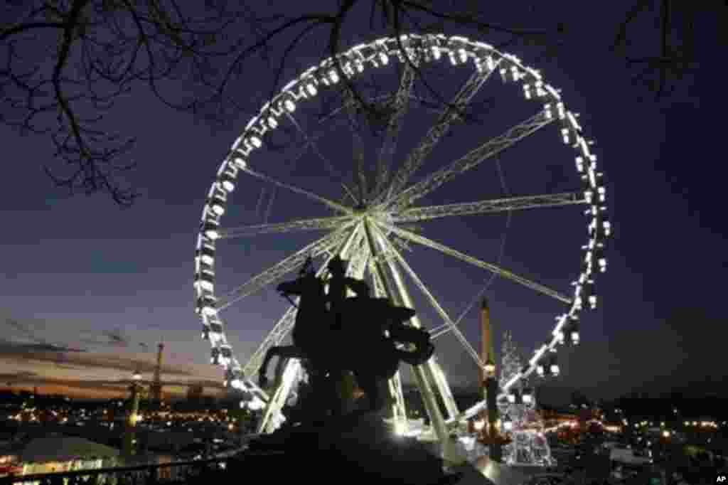 Night view of the ferris wheel set up for the Christmas period on the Place de la Concorde, in Paris, Wednesday Dec. 7, 2011. Visible at left is the Eiffel Tower.(AP Photo/Remy de la Mauviniere)