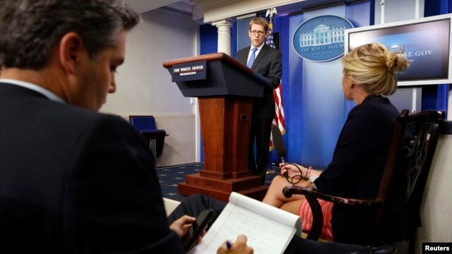A reporter takes notes as White House Press Secretary Jay Carney (C) answers his question about Syria during a press briefing at the White House in Washington, Aug. 27, 2013.