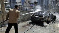 یک کارگر شهرداری شهر درعا در جنوب سوریه، به سمت یک خودروی آتش گرفته توسط معترضان آب می پاشد. ۱ فروردین ۱۳۹۰