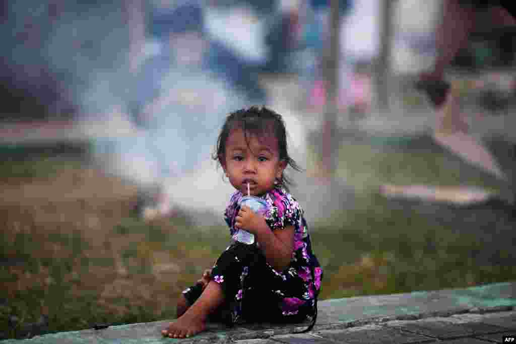 A child drinks water at a camp in Palu, in Indonesia's Central Sulawesi province, following the September 28 earthquake and tsunami.