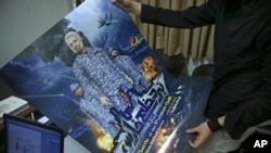 "A production assistant for the animated film, ""Battle of the Persian Gulf II,"" holds a poster for the movie, at the office of Farhad Azima, the Iranian director and screenwriter, in Tehran, Iran, Feb. 26, 2017."