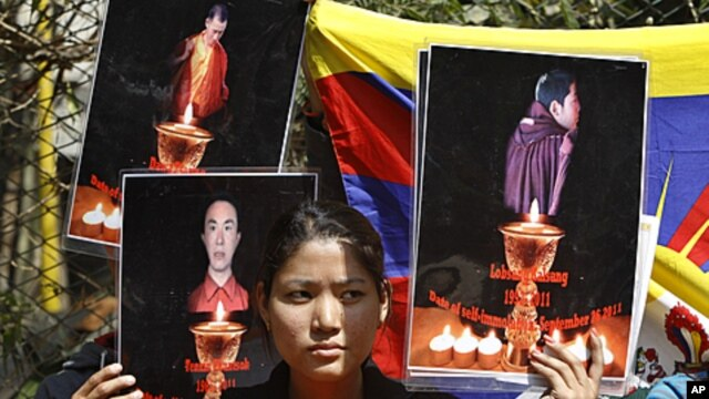 A Tibetan exile holds the photographs of Tibetan monks who have self immolated in Tibet protesting Chinese government, during a demonstration to support three fellow Tibetan exile students Tselo Gyal, 21, Lugoen Thar, 21, and Gyaltsen, 19 in Bangalore, In