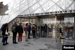 Pengunjung memasuki Piramida Louvre di Paris saat museum Louvre dibuka kembali untuk umum, setelah lebih dari enam bulan ditutup karena pandemi COVID-19 di Perancis, 19 Mei 2021.