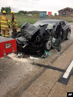 This May 11, 2018, photo released by the South Jordan (Utah) Police Department shows a traffic collision involving a Tesla Model S sedan with a Fire Department truck stopped at a red light. Witnesses indicated the Tesla Model S did not brake prior to impact.