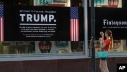一女子在赫爾辛基一家掛出歡迎川普總統和普京總統標語的店舖前拍照