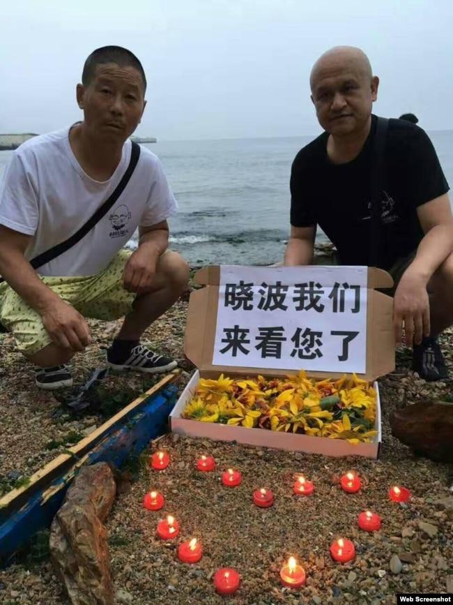 姜建军(左)、王承刚在大连老虎滩海边祭奠两天前葬于附近海域的刘晓波。(2017年7月17日 推特图片)