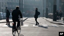 A cyclist pedals in downtown Milan, Italy, Monday, Dec. 28, 2015. Milan has ordered Monday a no-car day to combat pollution, which has hit unhealthy levels for weeks mainly because no rain has fallen to wash away the smog.