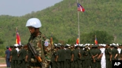 """A Cambodian army soldier, foreground, wears a U.N. helmet while standing guard during a U.S.-backed peacekeeping exercise dubbed """"Angkor Sentinel 2014"""" at the Cambodian tank command headquarters in Kampong Speu province, 60 kilometers (37 miles) west of Phnom Penh, file photo."""