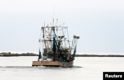 A Mississippi shrimp boat heads out of the harbor on the first day of shrimp season in Biloxi, Mississippi on June 3, 2010.