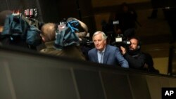 "European Union chief Brexit negotiator Michel Barnier, front, rides an escalator surrounded by the media on his way to a meeting at the Europa building in Brussels, Friday, Oct. 11, 2019. EU negotiator Michel Barnier says that he had a ""constructive…"