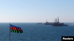 FILE - An Azerbaijan state flag flutters in the wind on an oil platform in the Caspian Sea east of Baku, Jan. 22, 2013.