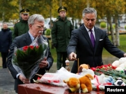 U.S. national security adviser John Bolton, left, and U.S. Ambassador to Russia Jon Huntsman attend a flower-laying ceremony at a World War II monument in Moscow to commemorate victims of a recent attack on a local college, Oct. 23, 2018.