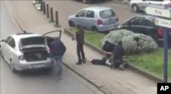 FILE - In this image made from video, police arrest a suspect in the terror attacks in the Anderlecht area of Brussels, April 8, 2016.