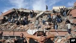 خهڵـکی ههوڵی ڕزگارکردنی قوربانیـیهکان دهدهن له ژێر داروپهردوی باڵهخانهیهکی داڕماو له گوندی Tabanli ی نزیک شـاری وان، یهکشهممه 23 ی دهی 2011