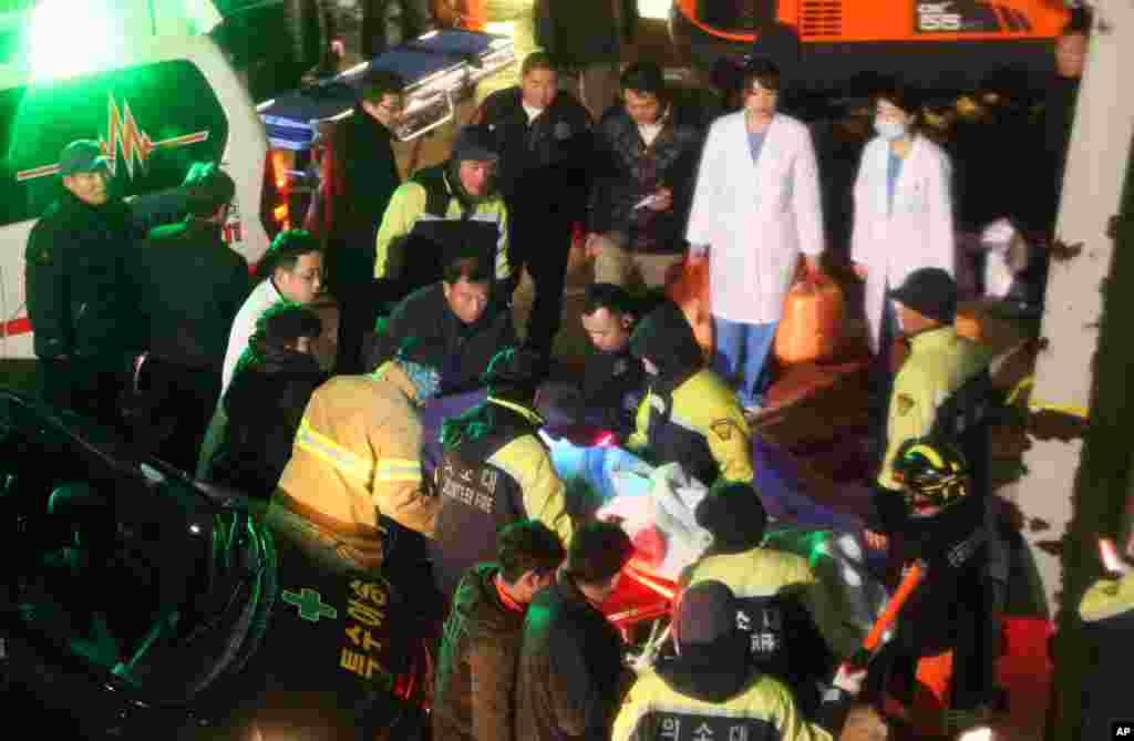 Rescue workers carry a victim, medical condition unknown, from a collapsed resort building in Gyeongju, South Korea, Feb. 17, 2014.