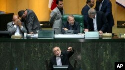 FILE - Head of Iran's Atomic Energy Organization Ali Akbar Salehi, bottom, speaks in an open session of parliament while discussing a bill on Iran's nuclear deal with world powers, in Tehran, Iran, Oct. 11, 2015.