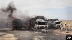 Nhân viên cứu hỏa Afghanistan phun nước vào xe tải của NATO bị đốt cháy ở Samagan, phía bắc thủ đô Kabul, ngày 18/7/2012