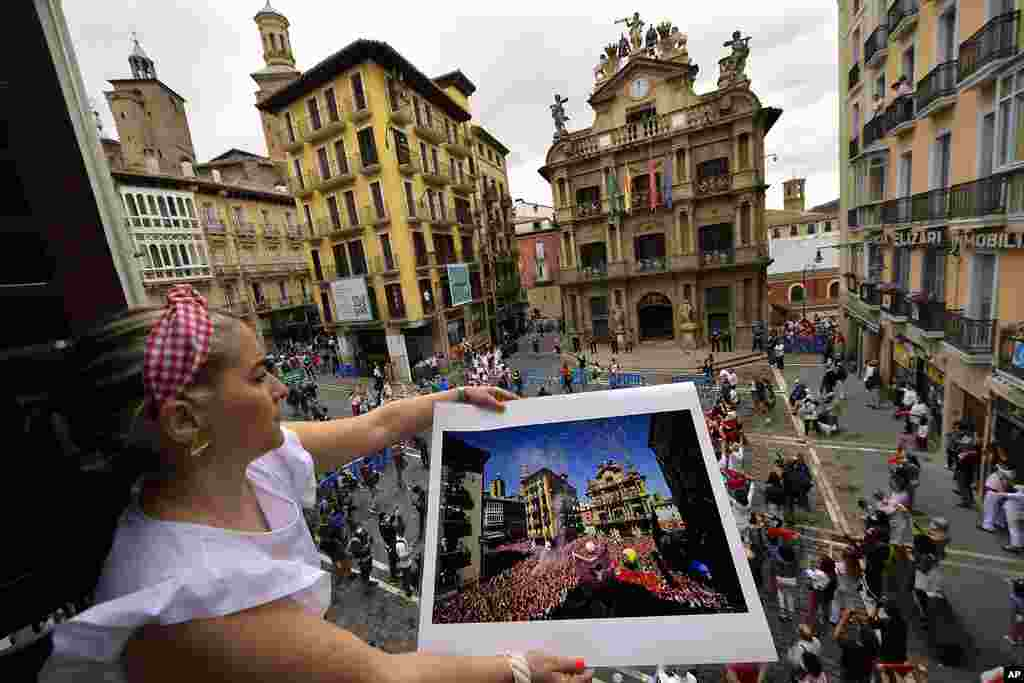 Cristina Esparza holds a San Fermin July 2019 photograph, in Pamplona, northern Spain, on the day the ''txupinazo'' would usually take place to start the famous San Fermin festival, which was canceled again this year due to the COVID-19 pandemic.