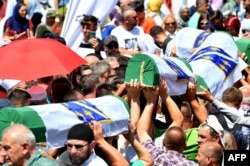 FILE - Bosnian Muslims carry caskets of the 33 newly identified bodies of the 1995 Srebrenica massacre before their inhumation at the Potocari Memorial Cemetery near the Eastern-Bosnian town of Srebrenica.