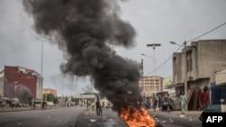 Des pneus brûlent alors que les manifestants barricadent les rues de Cadjehoun, fief de l'ancien président du Bénin, Thomas Yayi Boni, le 2 mai 2019 à Cotonou.
