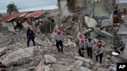 Ecuadorean firefighters comb through rubble of buildings destroyed by a 7.8-magnitude earthquake in Pedernales, April 22, 2016.
