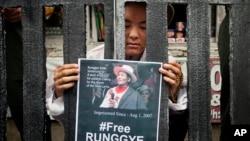 在印度达兰萨拉的一次街头表演中,一名流亡藏人在象征监狱的铁栏后举着被捕的荣杰阿扎的相片。(2014年8月1日)