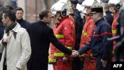 French President Emmanuel Macron (L) shakes hands with a firefighter during a visit in the streets of Paris on Dec. 2, 2018, a day after clashes during a protest of Yellow vests against rising oil prices and living costs.