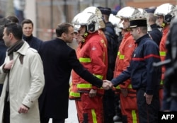 FILE - French President Emmanuel Macron (L) shakes hands with a firefighter during a visit in the streets of Paris on Dec. 2, 2018, a day after clashes during a protest of Yellow vests.