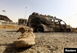 A burnt vehicle belonging to Iraqi security forces is pictured at a checkpoint in Mosul, one day after radical Sunni Muslim insurgents seized control of the city, June 11, 2014.