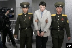 FILE - American student Otto Warmbier, center, is escorted at the Supreme Court in Pyongyang, North Korea, March 16, 2016. North Korea's highest court sentenced Warmbier to 15 years in prison after he allegedly attempted to steal a propaganda banner. Released and returned to the U.S. in a semi-comatose state in June, Warmbier died within days.