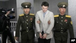FILE - American student Otto Warmbier is escorted at the Supreme Court in Pyongyang, North Korea, March 16, 2016. North Korea's highest court sentenced Warmbier to 15 years in prison after he allegedly attempted to steal a propaganda banner.