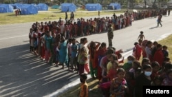 FILE - Women queue for food supplies at a camp for displaced earthquake victims in Kathmandu, Nepal, May 5, 2015.