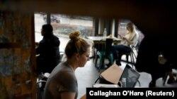 Kathryn Boeker bekerja dari sebuah kedai kopi di Texas ketika negara bagian itu mencabut aturan wajib masker dan membolehkan bisnis untuk kembali beroperasi dalam kapasitas normal di tengah pandemi virus corona di Houston, Texas, 10 Maret 2021. (Foto: Cal