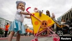 우크라이나 키예프에서 열린 유모자 퍼레이드에서 한 아기가 유모차를 잡고 서 있다. (자료사진)