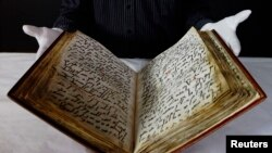 FILE - Senior Conservator of the British Library David Jacobs displays the library's 8th century Ma'il Qu'ran, one of the earliest in existance, during a media event at the British Museum in London, January 13, 2012.