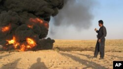 An Iraqi pipeline security guard inspects a damaged oil pipeline caused by a bomb explosion in the northern town of Kirkuk, 200 kilometers north of Baghdad, Iraq, Aug. 4, 2005.