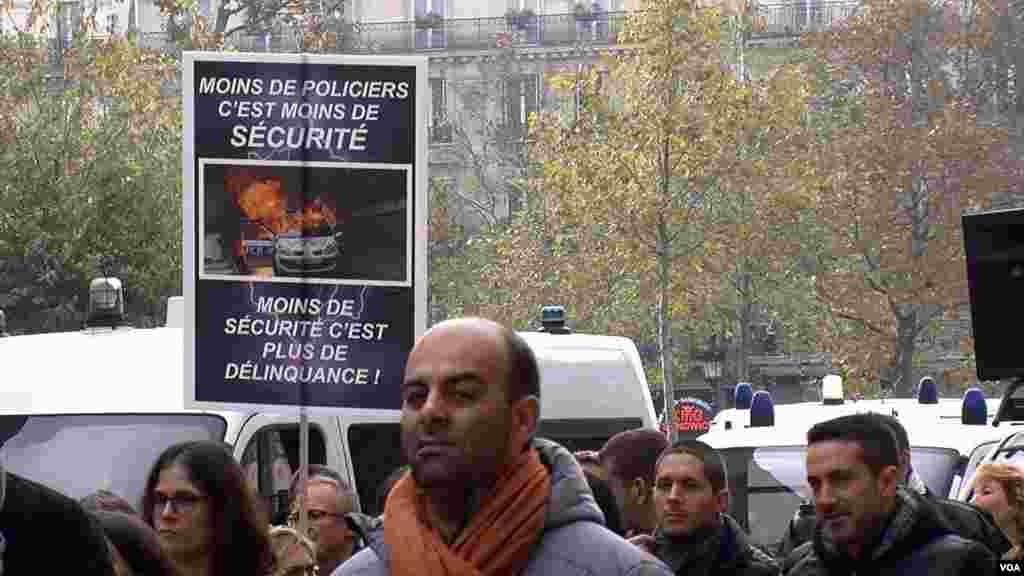 """Polisi berdemonstrasi di Paris dengan membawa poster, salah satunya bertuliskan """"Lebih sedikit polisi berarti berkurangnya keamanan"""" (26/10). (VOA/L. Bryant)"""