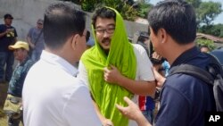 South Korean hostage Park Chul-hong (center) is greeted by unidentified officials as he prepares to board a plane for Davao city following his release Jan. 14, 2017, from his kidnappers in the volatile island of Jolo, southern Philippines. Park and Filipino companion Glen Alindajao were released Saturday after almost three months in captivity.