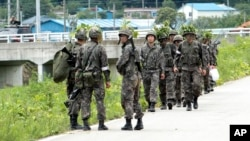 South Korean army soldiers patrol to search for a South Korean conscript soldier who is on the run after a shooting incident in Goseong, South Korea, Sunday, June 22, 2014.