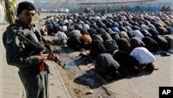 Un policier monte la garde tandis que des hommes prient à l'occasion de la Grande Fête, à Kaboul, Afghanistan