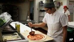 Andrea Ledesma es un graduado universitario, de 28 años, que trabaja haciendo pizzas en Milwaukee.