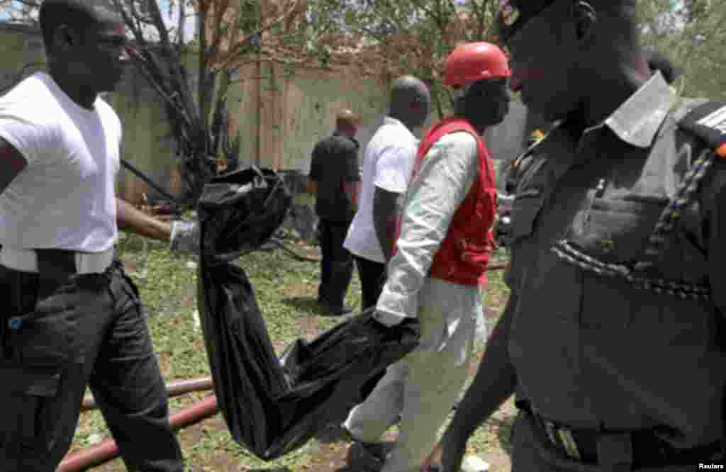 Rescue personnel recover mangled bodies wrapped in black polythene at the site of a bomb blast at This Day newspaper premises in Abuja April 26, 2012.