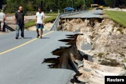 Người dân địa phương đi trên rìa một con đường đổ sập bên trên đập Hồ Patricia sau khi Bão Florence quét qua, ở Boiling Spring Lakes, North Carolina, ngày 19 tháng 9, 2018.