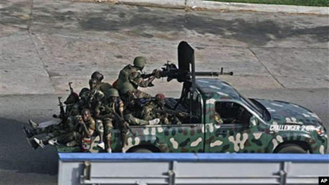 Unidentified troops drive past in the city of Abidjan, Ivory Coast, April 1, 2011