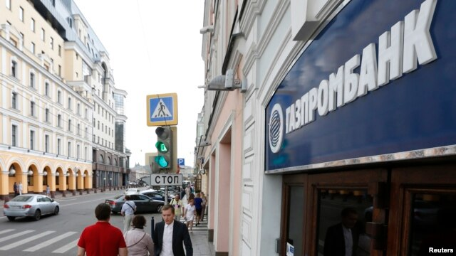 People walk past an office of Gazprombank, Russia's third-largest bank, in Moscow, July 17, 2014.
