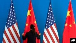 A Chinese woman adjusts the Chinese national flag near U.S. national flags, file photo.