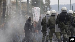A protester holds a hammer during clashes with riot police in Athens, Friday, Feb. 10, 2012.