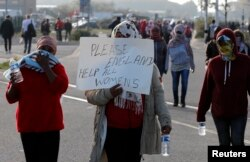 "Migrant women demonstrate on the second day of their evacuation and transfer to reception centers in France, as part of the dismantlement of the camp called ""the jungle"" in Calais, France, Oct. 25, 2016."