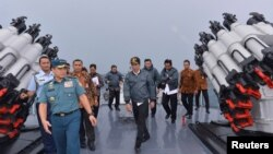 Presiden Joko Widodo di atas dek kapal Angkatan Laut KRI Imam Bonjol dengan beberapa anggota kabinet di perairan Kepulauan Natuna, Riau (23/6).