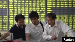 Investors talk at a brokerage house in Nantong, Jiangsu province, China, July 3, 2015. China's stock markets have had been decreasing since June.